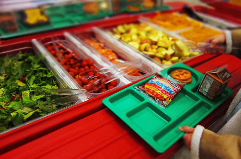 child holding lunch tray at salad bar