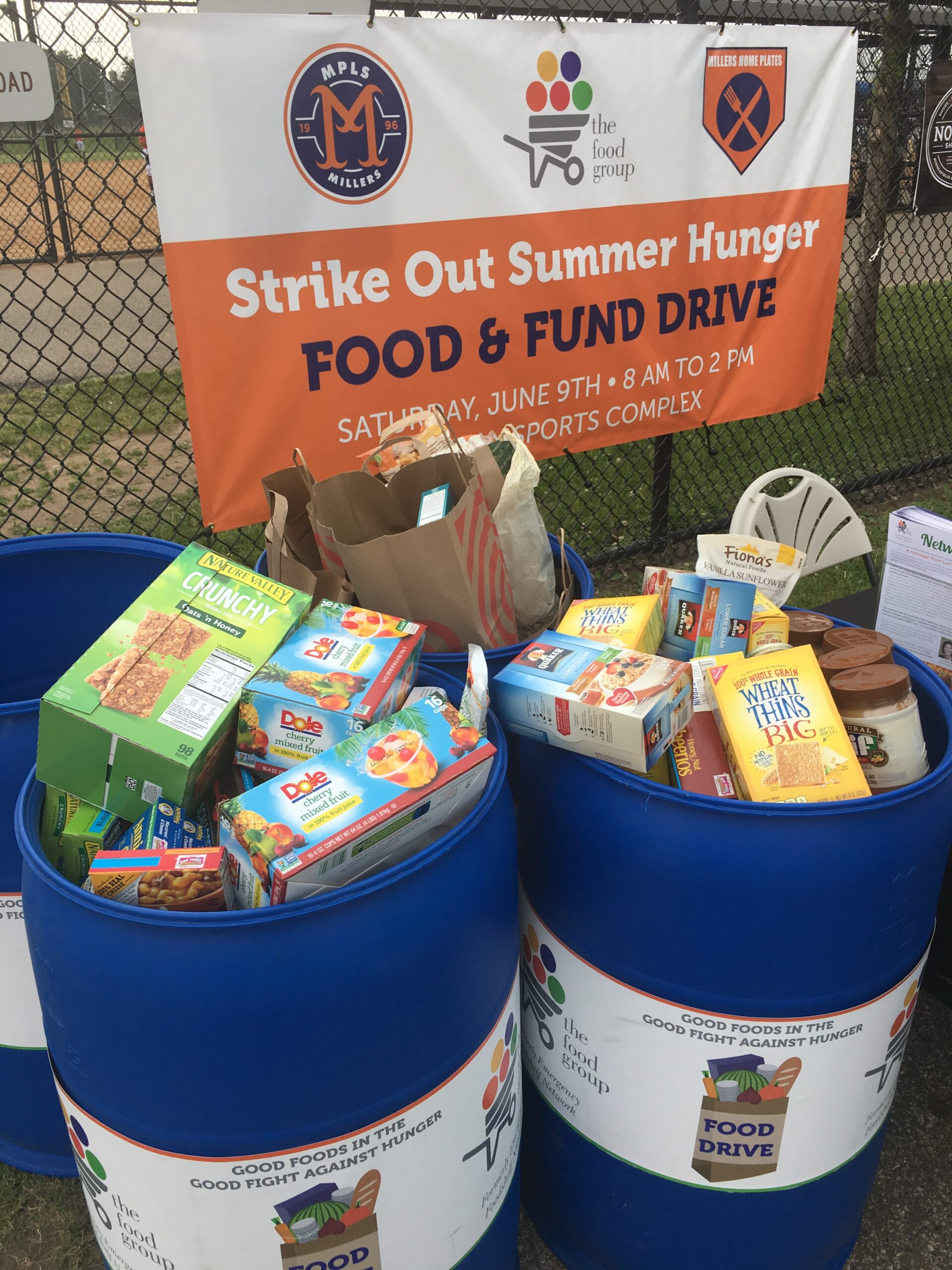 Blue collection bins at an outdoor food drive event filled with food donations