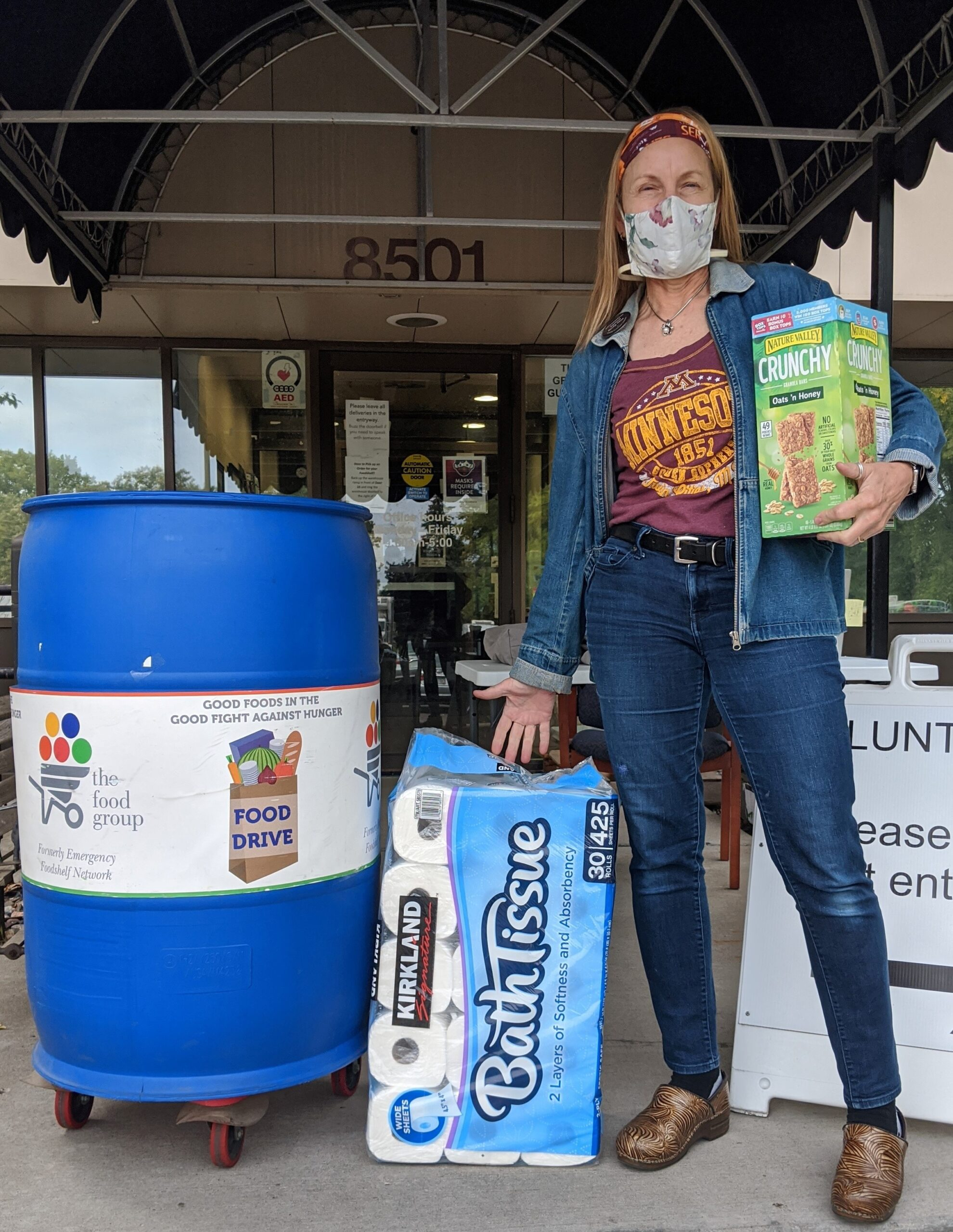 Woman standing in front of food drive collection bins, holding toilet paper and granola bars
