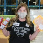 volunteer in warehouse holding up frozen packages of meat