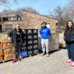 Three people standing in front of pallets of food in an outdoor parking lot while attending an outdoor food distribution